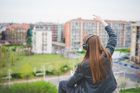 Rear view of young handsome eastern brunette girl listening music in a park in the city - technology, freedom, emancipation concept