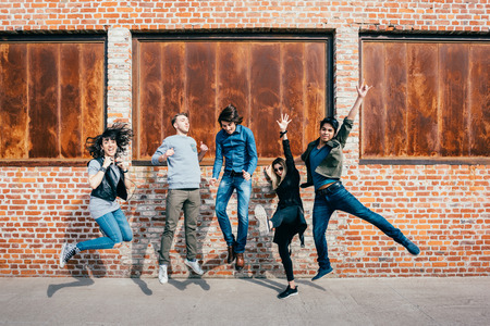 Photo pour Group of young beautiful multiethnic man and woman friends having fun jumping outdoor in the city - happiness, friendship, teamwork concept - image libre de droit