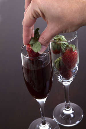 Female hand dipping a strawberry into a champagne flute filled with chocolate to make a sensual snack.