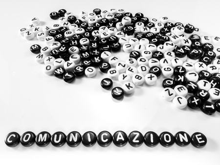 Foto per heap of round letters black and white and communication word written in italian written by side; comunicazione - Immagine Royalty Free