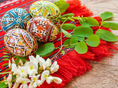 Photo pour nicely hand decorated romanian orthodox easter eggs with traditional motifs on a red cloth with acacia flowers aside - image libre de droit