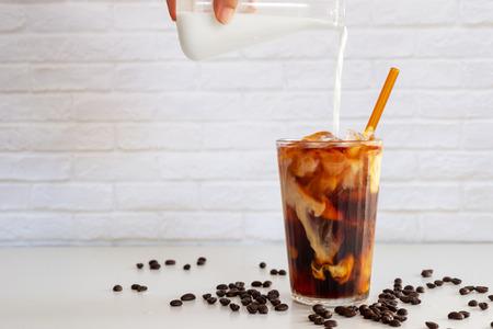 Foto de Pouring milk into a glass of homemade cold brew coffee on white table - Imagen libre de derechos
