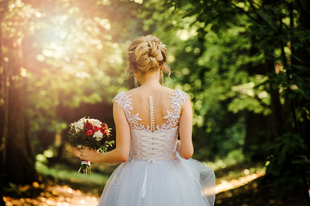 Photo pour back of the bride against the background of foliage and sunlight - image libre de droit