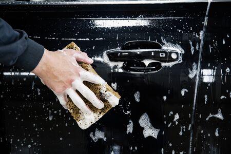 Photo pour car door with foam and a hand with a foam sponge - image libre de droit