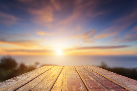 Close up top of old wooden table with blur sunset  background