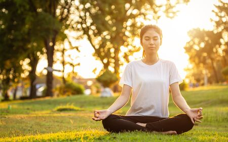 Photo for Pretty asian woman doing yoga exercises in the park. Used for relax and healthy concept - Royalty Free Image