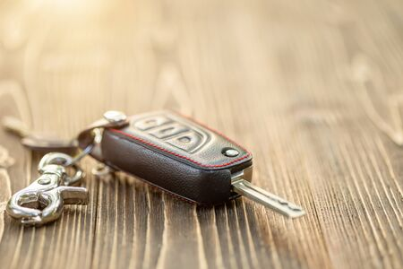 Photo for Close up new car keys with black leather cover on wooden table - Royalty Free Image