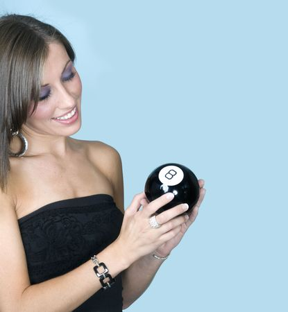 Attractive young woman looking at 8-ball for advice