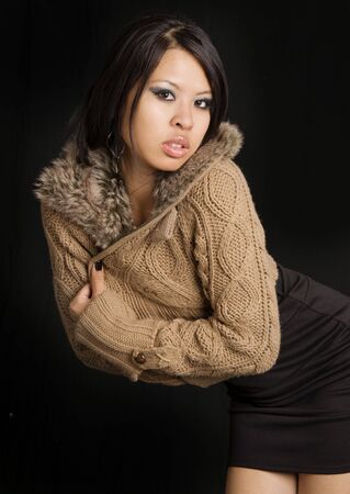 Attractive young woman wearing sweater with fur hood