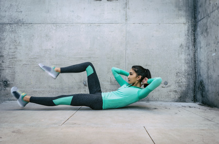 Young woman performing core crunch exercise gritty urban outdoor location
