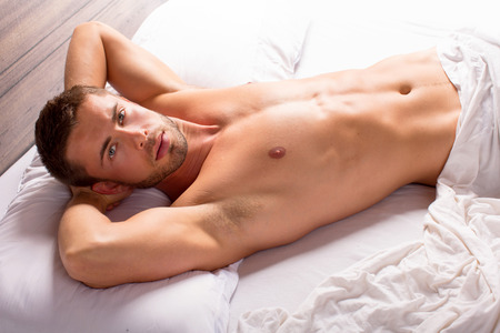 Photo pour Attractive young man laying in bed - image libre de droit
