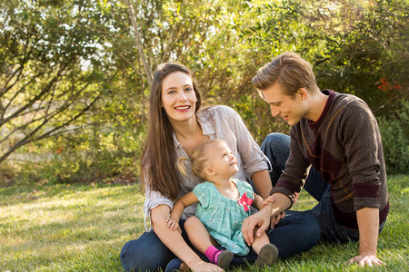 Happy young family sitting in the grass outside