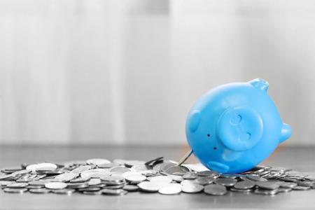 Photo pour Blue piggy bank on top of coins money for money flow concept and gray background. - image libre de droit