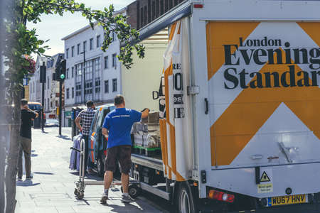Photo for London/UK-1/08/18: man unloading the London Evening Standard at The Quadrant in Richmond. The Evening Standard is a local, free daily newspaper, published Monday to Friday in tabloid format in London - Royalty Free Image