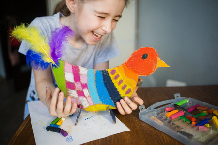 Foto de craft with kids. bright bird, cut from cardboard and painted with wax crayons,in the hands of a child. process of creating. - Imagen libre de derechos