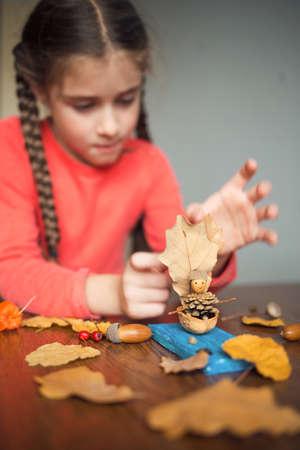 Foto de autumn craft with kids. children's cute boat with man made of natural materials. process of creating. - Imagen libre de derechos