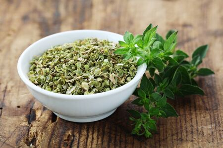 Photo for Dried Oregano In A White Bowl On A Wooden Background - Royalty Free Image