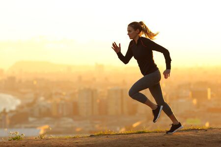 Foto de Side view full body portrait of a runner woman running in the outskirts of the city at sunset - Imagen libre de derechos