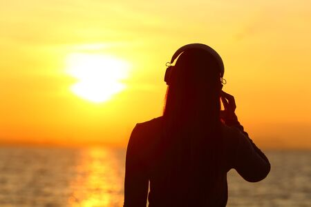Photo pour Silhouette of a girl wearing headphones listening to music at sunset on the beach - image libre de droit