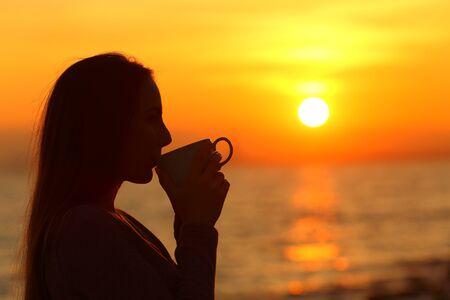 Photo pour Side view portrait od a woman silhouette drinking coffee at sunrise on the beach - image libre de droit