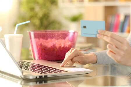 Photo for Close up of girl hands paying media content service with credit card and laptop on a desk at home - Royalty Free Image