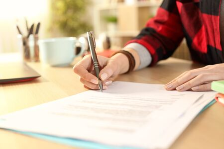 Photo for Close up of student girl hands signing contract on a desk at home - Royalty Free Image