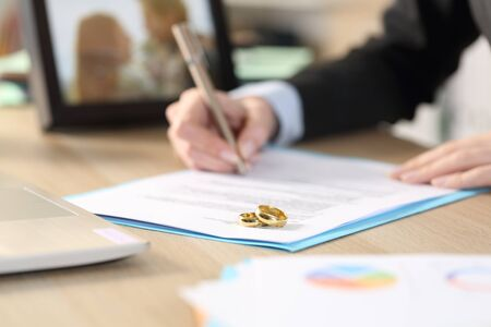 Photo pour Close up of self employed woman hands divorcing signing papers on a desk at home office - image libre de droit