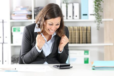 Photo pour Excited adult executive woman celebrating checking result on calculator sitting on a desk at office - image libre de droit