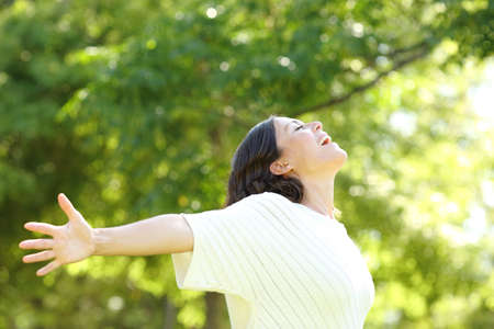 Photo for Happy adult woman breathing fresh air outstretching arms in the park at summer - Royalty Free Image