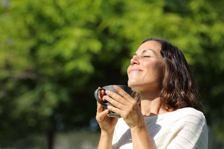 Photo for Satisfied adult woman smelling coffee cup standing in a green park at summer - Royalty Free Image