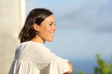 Foto de Mid aged woman contemplating views from a hotel balcony on summer vacation - Imagen libre de derechos