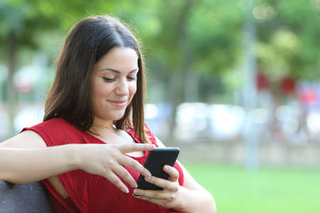 Photo pour Smiley woman in red checks smart phone sitting on a bench in a park - image libre de droit