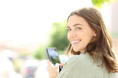 Photo pour Happy woman using mobile phone smiling at camera in the street - image libre de droit