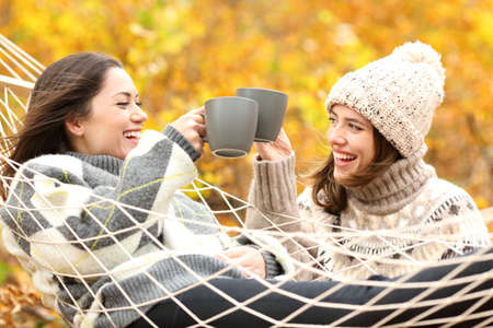 Photo for Two happy friends toasting with coffee cups in autumn holiday in a forest - Royalty Free Image
