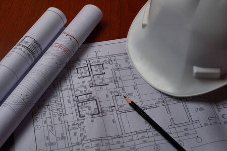 Foto de White hardhat and drawings at engineer workplace. - Imagen libre de derechos
