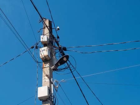Photo pour Concrete pole with lantern and lots of electric wires. - image libre de droit