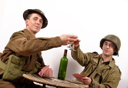 an English soldier and an American soldier drink a glass of wine and playind cards