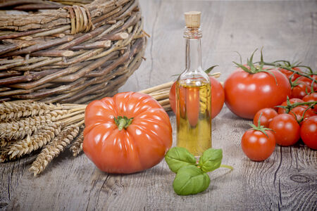 tomatoes with olive oil bottle on wooden tableの写真素材