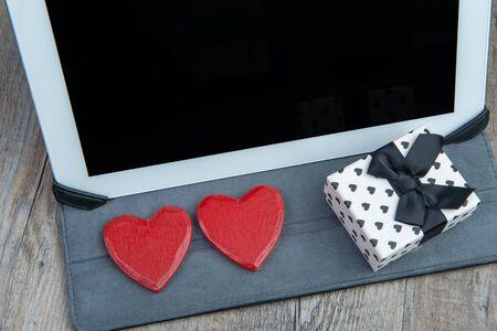 Photo pour a heart and a gift with a digital tablet - image libre de droit