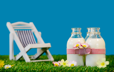 Photo pour Three small bottles of milk with a lounge chair in the grass - image libre de droit