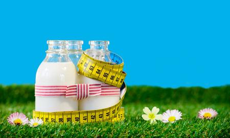 Photo pour Three small bottles of milk with a tape measure - image libre de droit