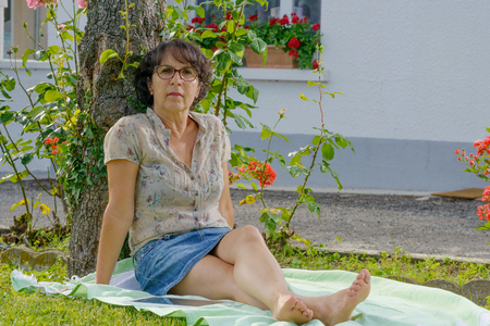 Foto für middle-aged woman with glasses is resting in the garden - Lizenzfreies Bild