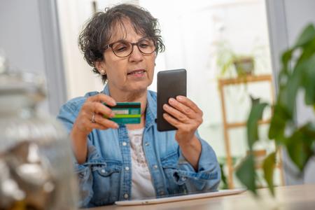 Photo pour a senior brunette woman shopping with internet - image libre de droit