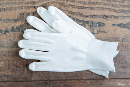 the white gloves on the wooden background