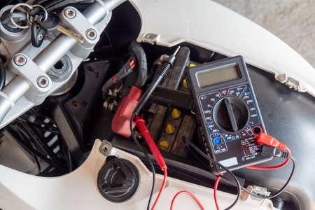 Photo pour a check volt of battery with motorcycle service concept - image libre de droit