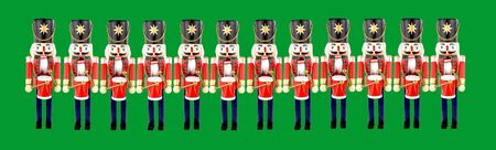Twelve traditional wooden soldier drummer Christmas decorations on a green background