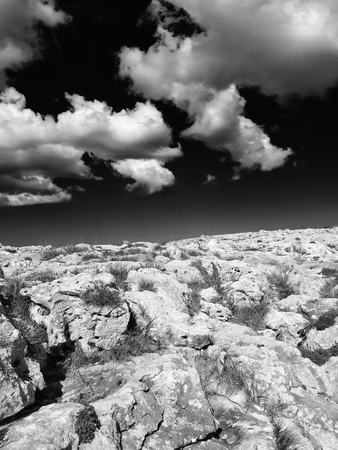 Photo pour monochome surreal image of a harsh rocky nanscape in bright light with dark contrasting sky and white clouds - image libre de droit