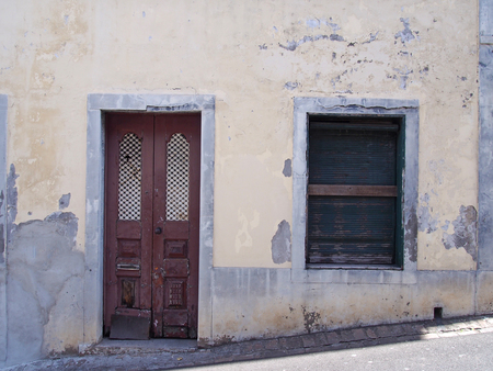 a run down empty abandoned house with crumbling yellow painted walls barred closed shutters and a broken wooden door on a sloping street in funchal portugal