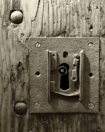 Photo pour A sepia monochome large square rusty iron lock with keyhole in an old wooden door and metal rivets - image libre de droit