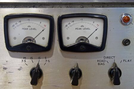 Photo for a close up of two old decibel meters on an old vintage reel to reel tape recorder with control knobs and switches - Royalty Free Image